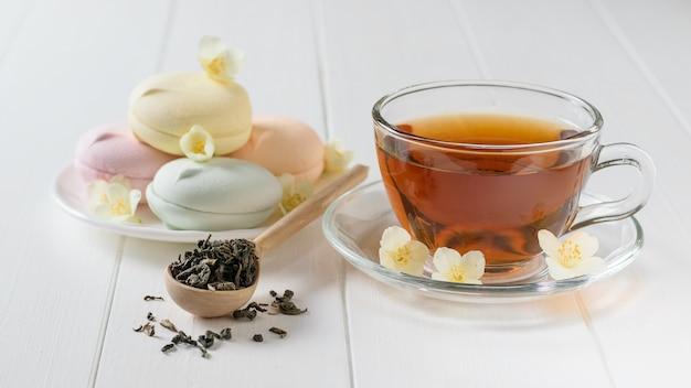 Wielokolorowe ptasie mleczko, herbata ziołowa i drewnianą łyżką na białym stole. skład porannego śniadania.
