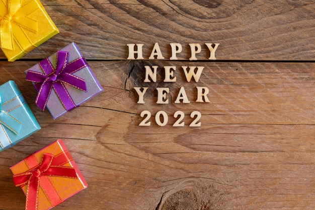 Wielokolorowe pudełka na prezenty. noworoczne prezenty na drewnianym stole. tex szczęśliwego nowego roku 2022. świąteczna kartka z życzeniami. leżał płasko.
