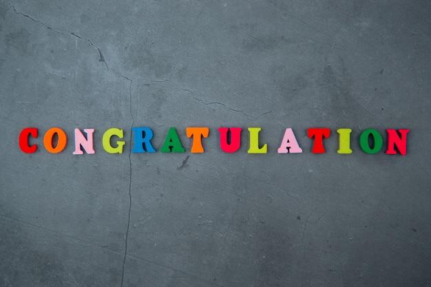 Wielokolorowe słowo gratulacyjne składa się z drewnianych liter na szarej otynkowanej ścianie.