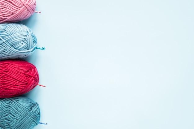 Wielokolorowe szydełka z kulkami z włóczki na niebieskim tle