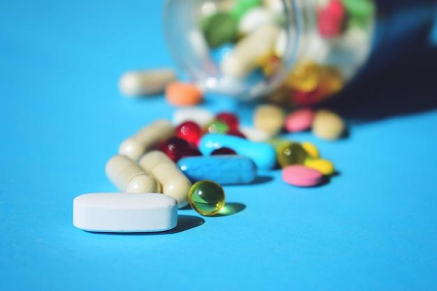 Wielokolorowe tabletki i kapsułki pigułki ze szklanej butelki na niebiesko