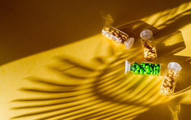 Wielokolorowe tabletki i kapsułki pigułki ze szklanej butelki na żółtym tle opieka zdrowotna close-up poziomy baner kopiowanie miejsca