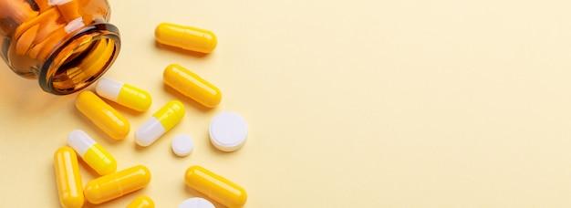 Wielokolorowe tabletki i pigułki kapsułki ze szklanej butelki na żółtym