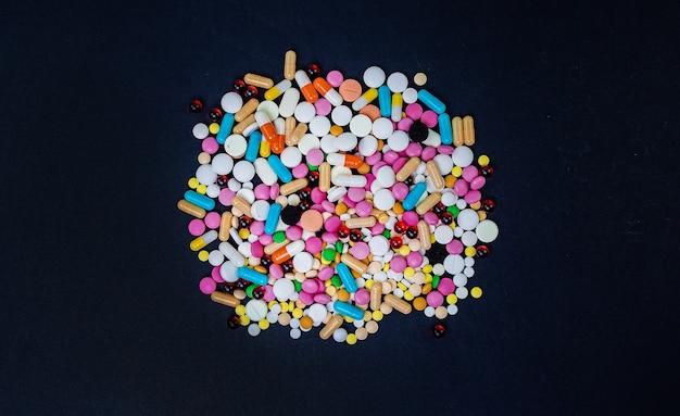 Wielokolorowe tabletki na czarnym tle