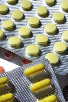 Wielokolorowe tabletki w blistrach foliowych leżą na jasnym tle. zbliżenie.