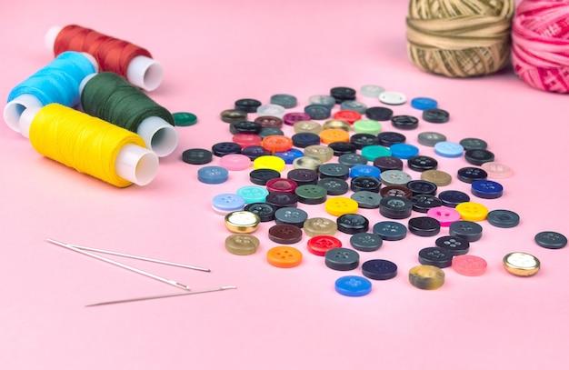 Wielokolorowe wątki i guziki na różowym tle. hobby, tło strony. kolorowe tło.