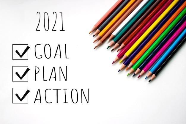 Wielokolorowe zaostrzone ołówki na białym tle z napisem 2021 cel plan działania