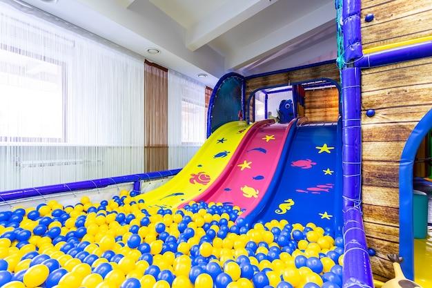 Wielokolorowe zjeżdżalnie dla dzieci z suchym basenem z ogromną ilością piłek. pusty plac zabaw