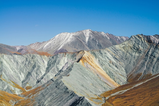 Wielokolorowy jesienny krajobraz z pokrytymi śniegiem górami i szarymi skalistymi skałami z pomarańczowym i liliowym odcieniem. spektakularny kolorowy widok na ostry grzbiet górski jesienią. motley górskiej scenerii w jesiennych kolorach.