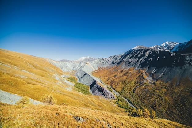 Wielokolorowy jesienny krajobraz z pokrytymi śniegiem górami i szarymi skalistymi skałami z pomarańczowym i liliowym odcieniem. spektakularny kolorowy widok na ostry grzbiet górski jesienią. pstrobarwna górska sceneria w jesiennych barwach