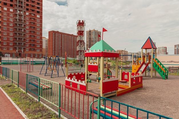 Wielokolorowy plac zabaw dla dzieci na tle ceglanych budynków i budowli