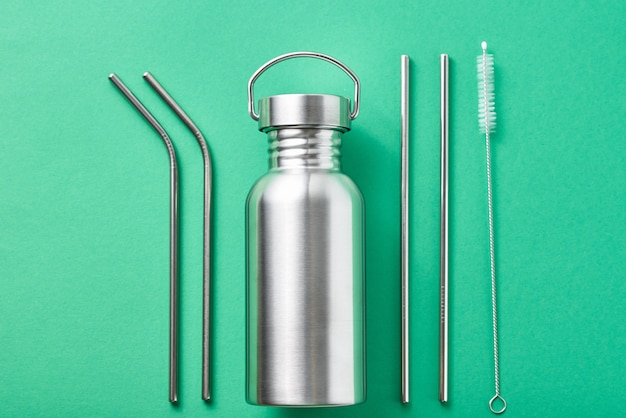 Wielokrotnego użytku plastikowe przedmioty bezpłatne na zielonym tle. widok z góry aluminiowej butelki i metalowych rurek.