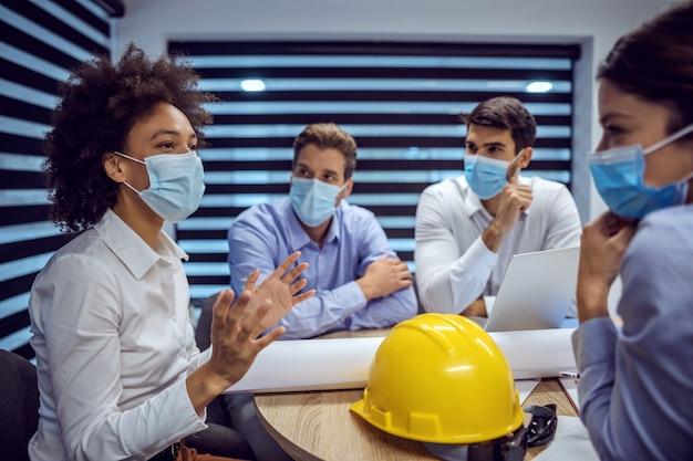 Wielokulturowa grupa architektów z maskami na twarzach siedząca w sali konferencyjnej i spotykająca się na temat nowego projektu podczas koronawirusa