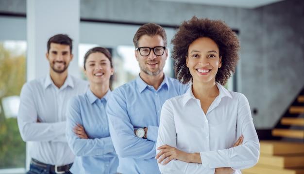 Wielokulturowa grupa ludzi biznesu stojących z rękami skrzyżowanymi w rzędzie. selektywne skupienie się na kobiecie rasy mieszanej.