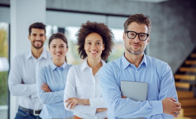 Wielokulturowa grupa ludzi biznesu stojących z rękami skrzyżowanymi w rzędzie
