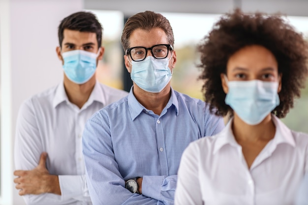 Wielokulturowa grupa ludzi biznesu z maskami na twarzach stojących z rękami skrzyżowanymi w firmie korporacyjnej.