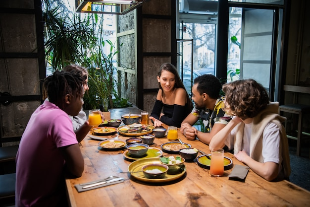 Wielokulturowa grupa młodych ludzi w kawiarni, jedzących azjatyckie jedzenie, pijących koktajle, rozmawiających
