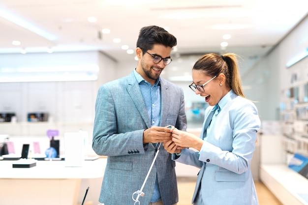 Wielokulturowa para ubrana w garnitur, wybierając nowy zegarek na rękę. wnętrze sklepu technicznego.