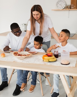 Wielokulturowa rodzina je pizzę