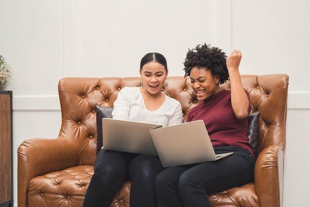 Wielokulturowe kobiety korzystające z laptopa na kanapie, relaksujące się w salonie i śmiejące się z czegoś na ekranie