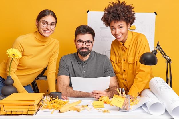 Wielokulturowi koledzy współpracują przy projektach projektowych omawiają pomysły na ilustrację pozują razem na brudnym pulpicie rysują plany mają szczęśliwe wyrazy twarzy spędzają dzień w miejscu pracy rozwijają projekty