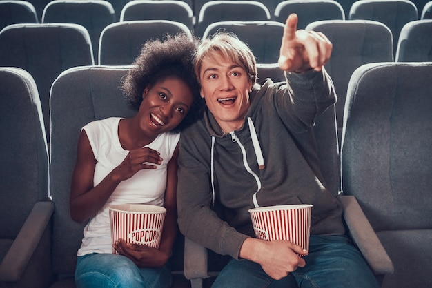 Wielonarodowa para ogląda komedię w kinie.