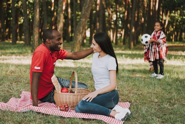 Wielonarodowa para usiąść na obrusie na pikniku.