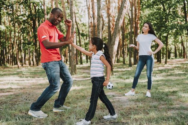 Wielonarodowa rodzina gra z piłką w lesie.