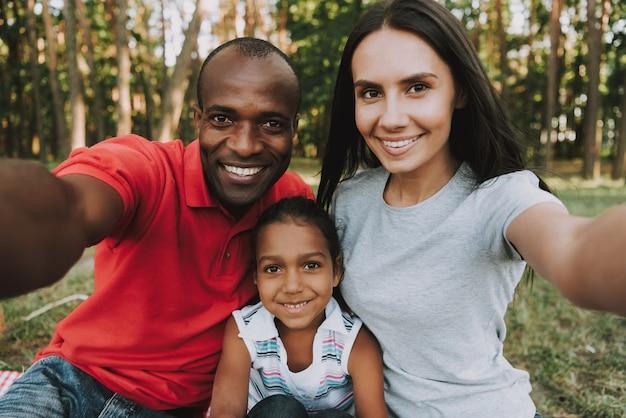 Wielonarodowa rodzina robi selfie na pikniku.