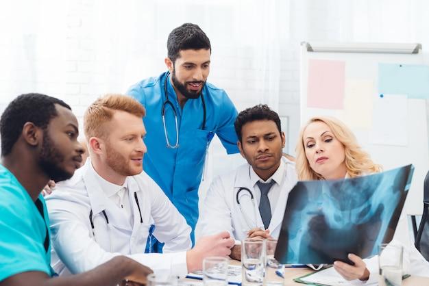 Wielonarodowi lekarze. wyniki badania rentgenowskiego pacjenta.