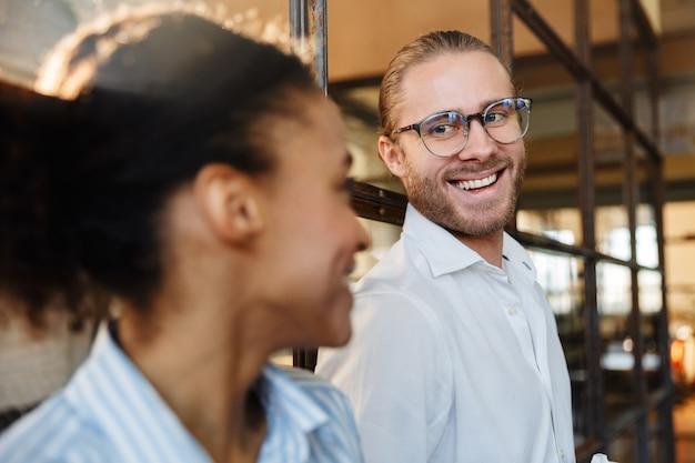 Wielonarodowi, radośni koledzy rozmawiający i śmiejący się podczas pracy w biurze