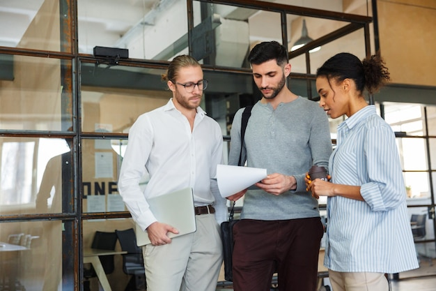 Wielonarodowi skoncentrowani koledzy rozmawiają i czytają dokumenty podczas chodzenia z laptopami w nowoczesnym biurze