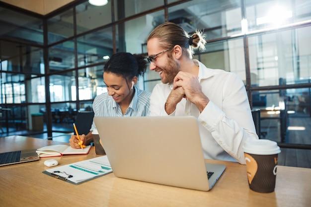 Wielonarodowi uśmiechnięci koledzy pracujący z laptopami i pijący kawę siedząc przy stole w biurze