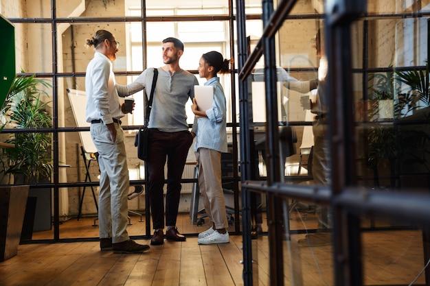 Wielonarodowi zadowoleni koledzy rozmawiają i uśmiechają się stojąc z laptopem w nowoczesnym biurze