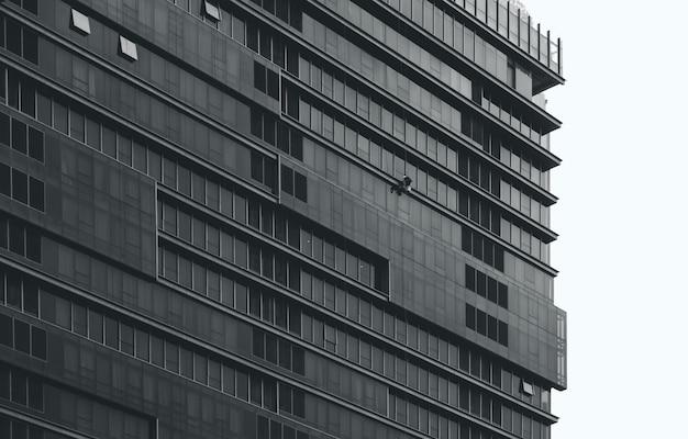 Wielopiętrowy budynek biurowy z pracownikiem czyszczenia szyby