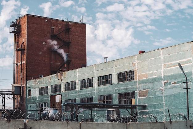 Wielopiętrowy budynek produkcyjny za płotem z drutem kolczastym. malownicza stara odnowiona działająca fabryka. starzejący się obiekt przemysłowy. duży wieżowiec produkcyjny. zamknięty teren przemysłowy zakończenie.
