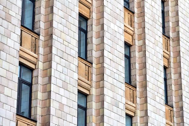 Wielopiętrowy budynek. rytm w fotografii. wielokondygnacyjna fasada, okna i blok mieszkalny