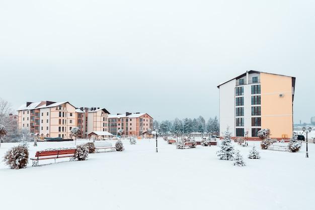 Wielopiętrowy budynek w pobliżu pięknego parku zimowego
