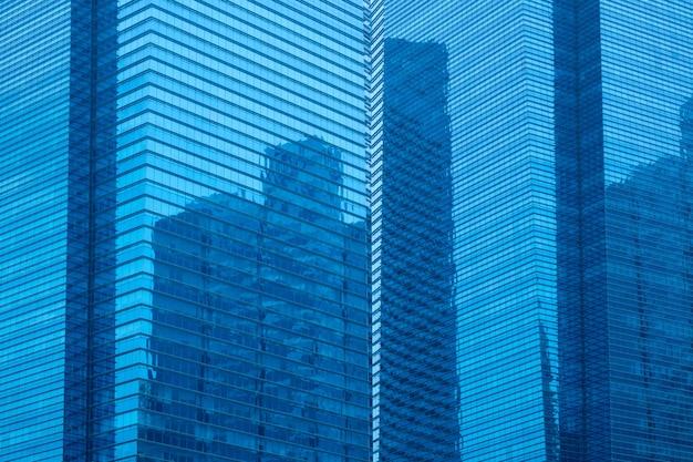 Wielopiętrowy wieżowiec ze szklanymi fasadami i odbiciem innego wieżowca