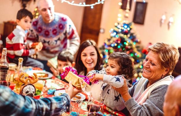 Wielopokoleniowa duża rodzina bawi się na przyjęciu wigilijnym - zimowe wakacje x koncepcja masowa z rodzicami i dziećmi jedzącymi razem otwierającymi prezenty w domu - skup się na małej córce - ciepły filtr