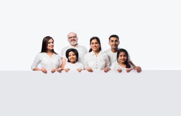 Wielopokoleniowa indyjska azjatycka rodzina z białą tablicą, wskazującą lub przedstawiającą pustą białą tabliczkę