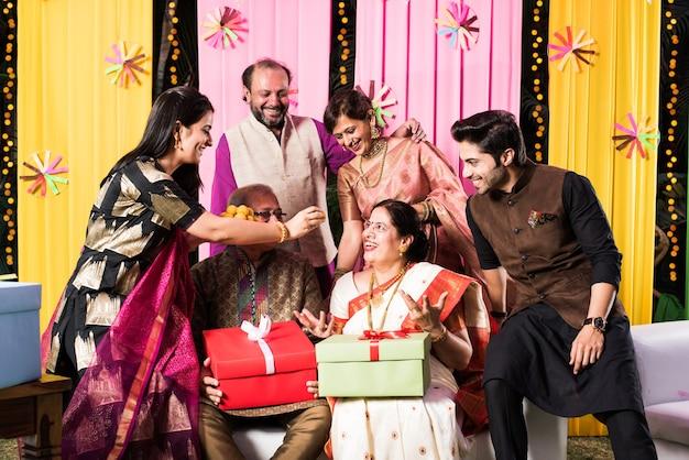 Wielopokoleniowa indyjska rodzina jedząca słodycze podczas świętowania lub okazji, ubrana w tradycyjny strój, siedząca na kanapie lub kanapie