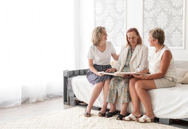 Wielopokoleniowa kobieta siedzi na kanapie patrząc na album fotograficzny rodziny