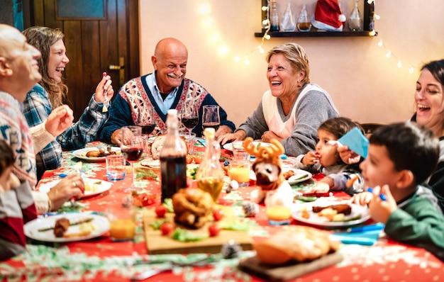 Wielopokoleniowa rodzina bawi się podczas świątecznego obiadu - zimowe wakacje i koncepcja x mas o dziadkach jedzących razem z dziećmi podczas domowej kolacji - skoncentruj się na babci po prawej stronie