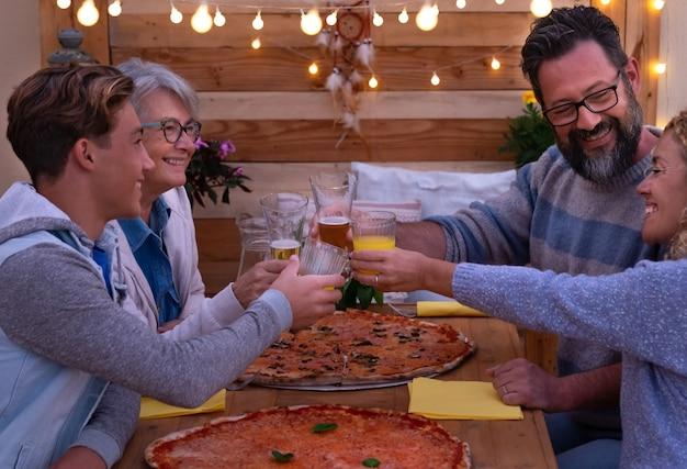 Wielopokoleniowa rodzina dzieli się razem dużą pizzą i grzankami drewniany stół i tło