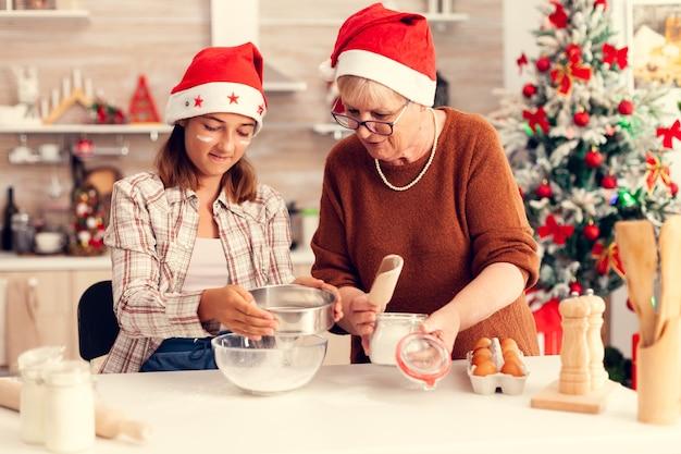 Wielopokoleniowa rodzina robi razem ciasteczka w boże narodzenie