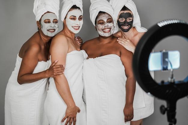 Wielopokoleniowe kobiety noszące maski na twarz podczas przesyłania strumieniowego wideo online za pomocą telefonu komórkowego -