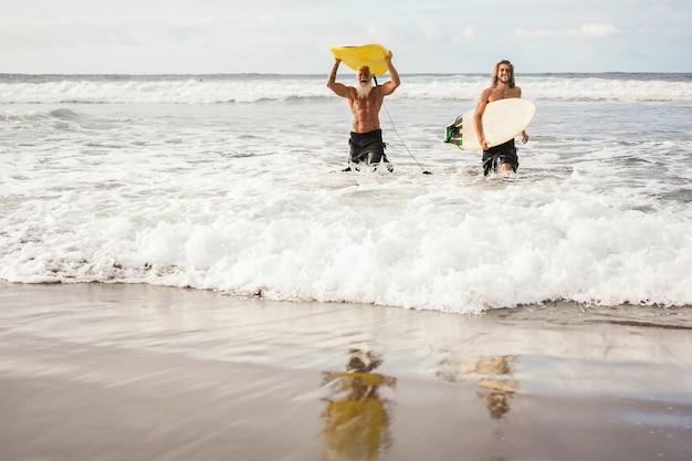 Wielopokoleniowi przyjaciele bawią się podczas surfowania na plaży na wyspie - skup się na właściwym facecie