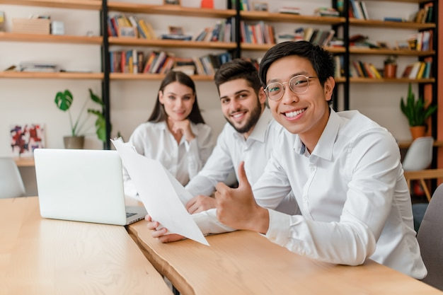 Wielorasowa grupa biznesmeni dyskutuje biznes w biurze