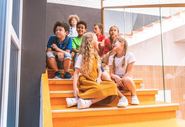 Wielorasowa grupa dzieci w szkole podstawowej - zabawni uczniowie cieszący się czasem szkolnym i lekcją z nauczycielem i kolegami z klasy